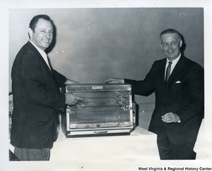 An unidentified man showing Congressman Arch Moore, Jr. what looks to be a toaster oven.