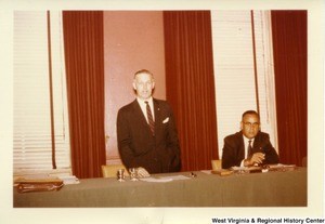 Congressman Arch Moore, Jr. standing behind a table talking. An unidentified man is sitting next to him.