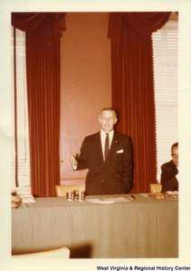 Congressman Arch Moore, Jr. standing behind a table talking.