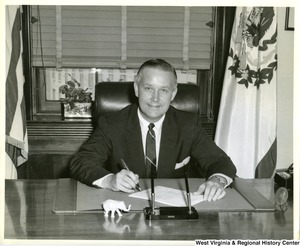 Congressman Arch Moore, Jr. sitting behind his desk signing a letter.
