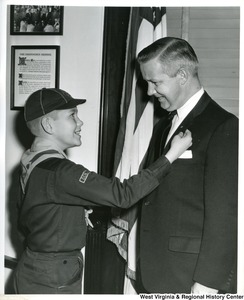A unidentified Boy Scout is pinning a pin to the lapel of Congressman Arch Moore, Jr.'s jacket.