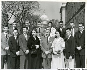Congressman Arch Moore, Jr. (middle front) with a group of unidentified men and women. The Capitol Building can be seen in the background.