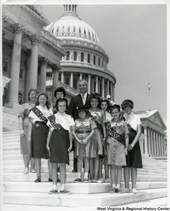 A Girl Scout troop stands with Congressman Arch Moore, Jr. on the steps of the Capitol Building.