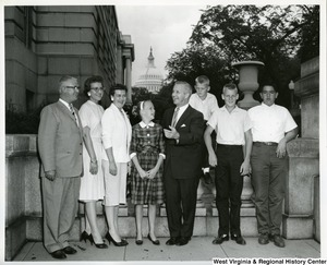 Congressman Arch Moore, Jr. standing in the center with three unidentified boys on the right and three unidentified adults and one unidentified girl on the left. The Capitol Building can be seen in the background.
