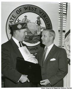 "Congressman Arch Moore, Jr. with a member of The Veterans Of Foreign Wars. Moore is holding a paper stating, ""Dedication, National Memorial Building, 200 Maryland Ave, N.E. Washington, D.C., February 8, 1963"""