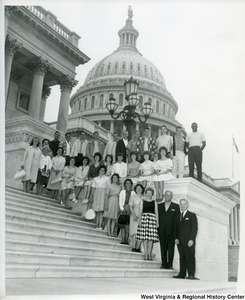 Congressman Arch Moore, Jr., on the end (right), with a group of unidentified people sitting and standing on the Capitol Building steps.