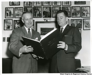 Congressman Arch Moore, Jr. looking at a large book with an unidentified man.