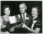Congressman Arch Moore, Jr. with two unidentified women looking at a book on West Virginia. The back of the photograph states the photo was taken at the House Office Building, Washington, D.C.
