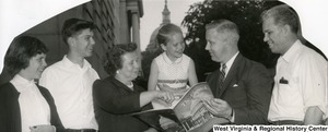 "Congressman Arch Moore, Jr. showing an unidentified family a magazine or pamphlet titled, ""The Capitol."" This photograph has been cut, most likely for the Congressman's newsletter.  The Capitol Building can be seen in the background."