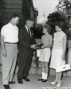 Congressman Arch Moore, Jr. signing a picture of the Capitol Building for a unidentified girl. A man and woman, probably her mother and father, stand on either side of her and Moore. The Capitol Building can be seen in the background.