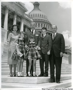 Congressman Arch Moore, Jr. (center) with an unidentified family standing on the steps of the Capitol building.