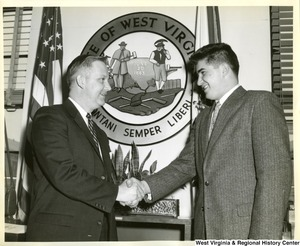 Congressman Arch Moore, Jr. shaking the hand of a unidentified man. The West Virginia seal is in the background.