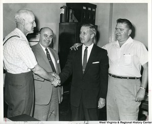 Congressman Arch Moore, Jr. shaking the hand of a unidentified man. Another man has his arm around Moore's shoulder. The third man is standing between Moore and the unidentified man who is shaking his hand.