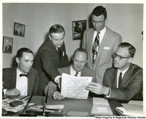 Congressman Arch Moore, Jr. leaning over the shoulder of a unidentified man pointing at a map of Ohio-West Virginia border. Three other unidentified men are also looking at the map.