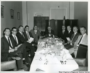 Congressman Arch Moore, Jr. at a lunch or breakfast meeting. Moore is at the head of the table. There are five unidentified men on the left side of the table and four unidentified men on the right side of the table.