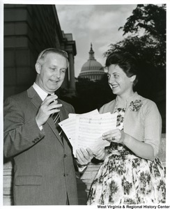 Congressman Arch Moore, Jr. with an unidentified woman who is showing him sheets of music. The Capitol Building can be seen in the background.