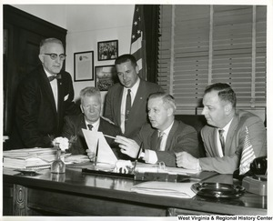 Congressman Arch Moore, Jr. sitting at his desk going over a document with four other unidentified individuals.
