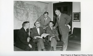Congressman Arch Moore, Jr. and a group of unidentified men looking through a document. Moore is the first on the left. A map of the United States is in the background.