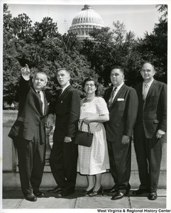 Congressman Arch Moore, Jr. pointing at something with a group of four unidentified individuals. The Capitol Building is in the background.