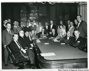 Congressman Arch Moore, Jr., is seated first on the right. Also pictured are Reps. McCulloch, seated second right, Riehlman, seated third right, Hill, seated fourth right, Patman, seated center, Evins standing fourth on the left, and Multer, seated third on the left. The remaining individuals in the photograph are unidentified.