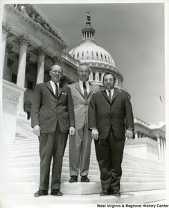 Congressman Arch Moore, Jr. standing on the steps of the Capitol Building with two unidentified men.
