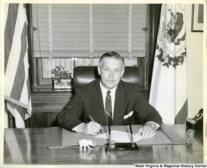 Congressman Arch Moore, Jr. sitting at his desk signing a document.
