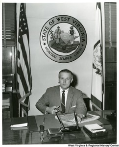 Congressman Arch Moore, Jr. sitting at his desk cutting clips from a Wheeling newspaper.
