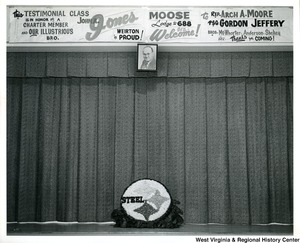 "A photograph of the Steelmark logo on a stage. At the top of the photo is a banner stating ""This testimonial class is in honor of a charter member and our illustrious bro. Weirton is Proud! John A. Jones. Moose Lodge No. 688 Sez- Welcome! to Rep. Arch A. Moore, P.S.G. Gordon Jeffery, and Bros. McWhorter, Anderson, Shekey. Sez --- thanks for coming!"""