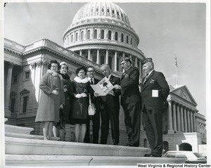 "Congressman Arch A. Moore, Jr. looking at a book, ""Operation Vietnam Honor Roll,"" created by the Memorial City Post 3081 & Ladies Auxiliary, with unidentified members of the Veterans of Foreign Wars. They are standing on the steps of the Capitol Building."