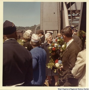 A group of unidentified individuals are standing on the Market Street Bridge (Brooke County, W.V.). Some are holding flowers.