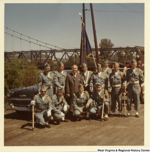 Congressman Arch A. Moore, Jr. (center) with an unidentified honor guard. They are standing in front of a vehicle, and the Market Street Bridge can be seen in the background.