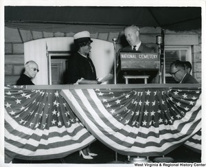 "Congressman Arch A. Moore, Jr. talking with an unidentified African American woman while standing at a podium. The podium has a sign that reads, ""National Cemetery.""  Two unidentified men are sitting on both sides of Moore."