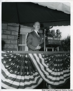 "Congressman Arch A. Moore, Jr. standing at a podium with a sign that reads, ""National Cemetery."""