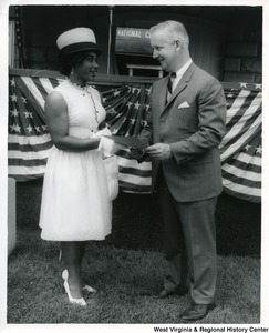 Congressman Arch A. Moore, Jr. hands a document to an unidentified African American woman at the National Cemetery.