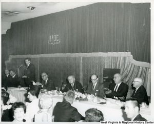 Congressman Arch Moore, Jr. sitting with unidentified members of the Iron Workers Local Union No. 549 at the Silver Anniversary Banquet. The banquet was held at the Elks Lodge in Wheeling, W.V.