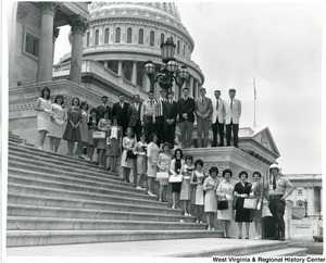 A group of men and women lined up on the Capitol building steps. An officer is the last person and is standing at the bottom of the stairs.