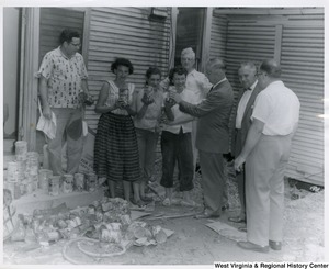 Three women and one man are standing in front of a building showing Congressman Arch A. Moore, Jr. large cans of tomato juice. There are stacks and piles of cans on the ground next to them.