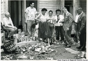 Three unidentified women are showing Congressman Arch A. Moore, Jr.damaged canned tomato juice. On the ground around them are stacks and piles of other canned goods.  An unidentified woman is sitting on the left side of the photo and three other unidentified men are present.