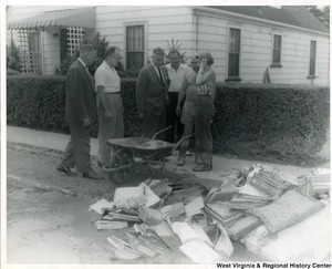 Congressman Arch A. Moore, Jr. surveying damaged goods that are piled in front of a house. Three unidentified people are standing with Moore.