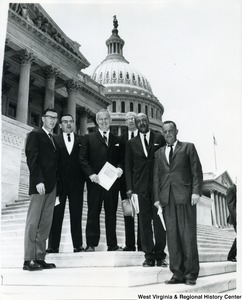Congressman Arch A. Moore, Jr. (center) with five unidentified men on the steps of the Capitol Building.