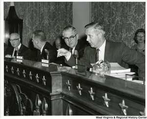Congressman Arch A. Moore, Jr. examining a witness during a hearing before a subcommittee of the Select Committee on Small Business, on low cost residual fuel oil and crude oil imports. On Moore's right is Congressman Tom Steed of Oklahoma, Chairman of the Sub-committee, J. Allan Sherier and Justinius Gould, Counsels of the Committee.