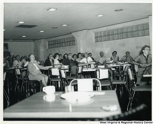 An unidentified group of people sitting at tables and listening to Congressman Moore, who is not shown in the picture.