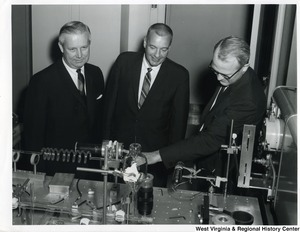 Congressman Arch A. Moore, Jr., with Mr. M.C. Hunt of the Chesapeake and Potomac Telephone Co. of W.Va., visiting one of the major locations of Bell Telephone Laboratories, in Murray Hill, New Jersey, research and development unit of the Bell Systems.  They are discussing an infrared optical maser in the Solid State Electronics Research Laboratory. From left to right: Congressman Moore; Mr. Hunt, Executive Assistant at Chesapeake and Potomac Telephone Co. of W.Va.; and Dr. John X. Galt, Director of Solid State Electronic Research Laboratory at Bell Telephone Laboratories.