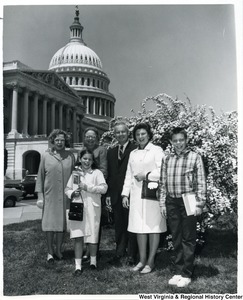 Congressman Arch A. Moore, Jr. (center) standing with an unidentified family in front of a blooming bush. The Capitol Building can be seen in the background.