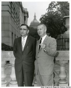Congressman Arch A. Moore, Jr. pointing something out to an unidentified man. The capitol building is in the background.