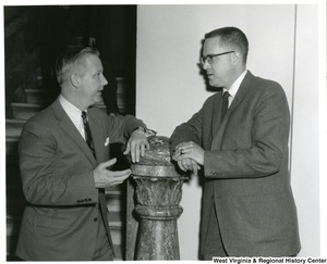 Congressman Arch A. Moore, Jr. leaning on a marble pillar talking to an unidentified man.