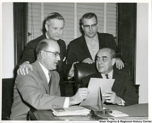 Congressman Arch A. Moore, Jr. (back, left) looking over and discussing a document with three other unidentified men.