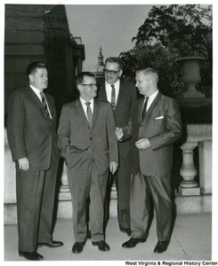 Congressman Arch A. Moore, Jr. talking to three unidentified men. The Capitol building can be seen in the background.