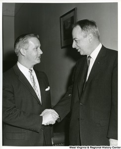 Congressman Arch A. Moore, Jr. shaking hands with an unidentified man.