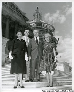 Congressman Arch A. Moore, Jr. (center) with two unidentified women and one man on the steps of the Capitol Building. The Capitol dome can be seen under construction.